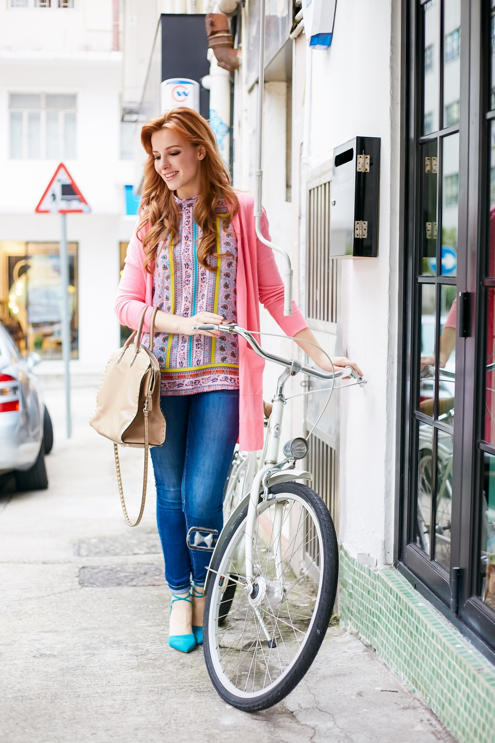 Redhead wearing pink, valentino rockstud dome satchel, bicycle