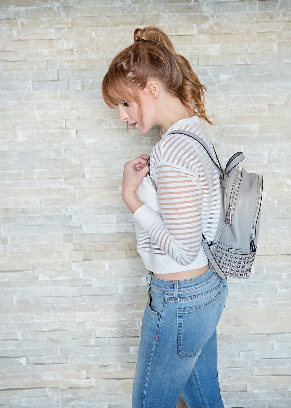 redhead wearing a michael kors backpack