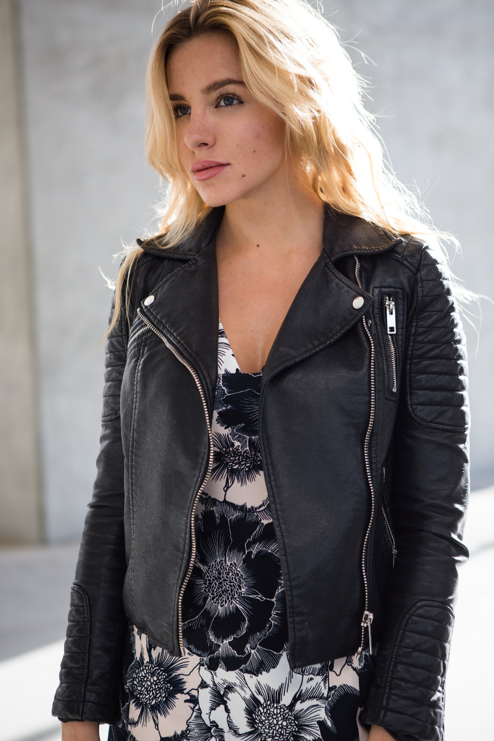 blonde girl wearing leather jacket and floral dress