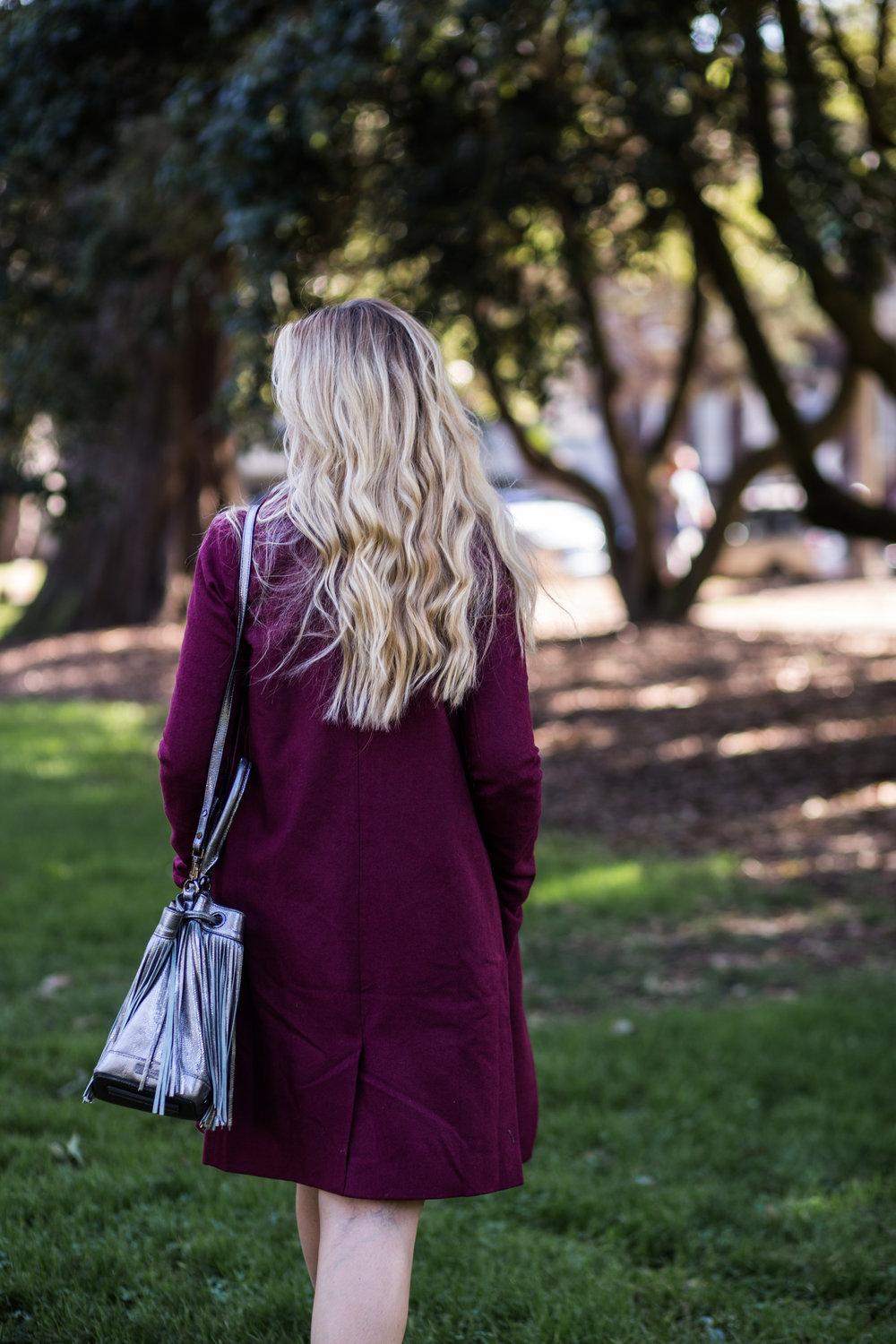 blonde wearing burgundy coat