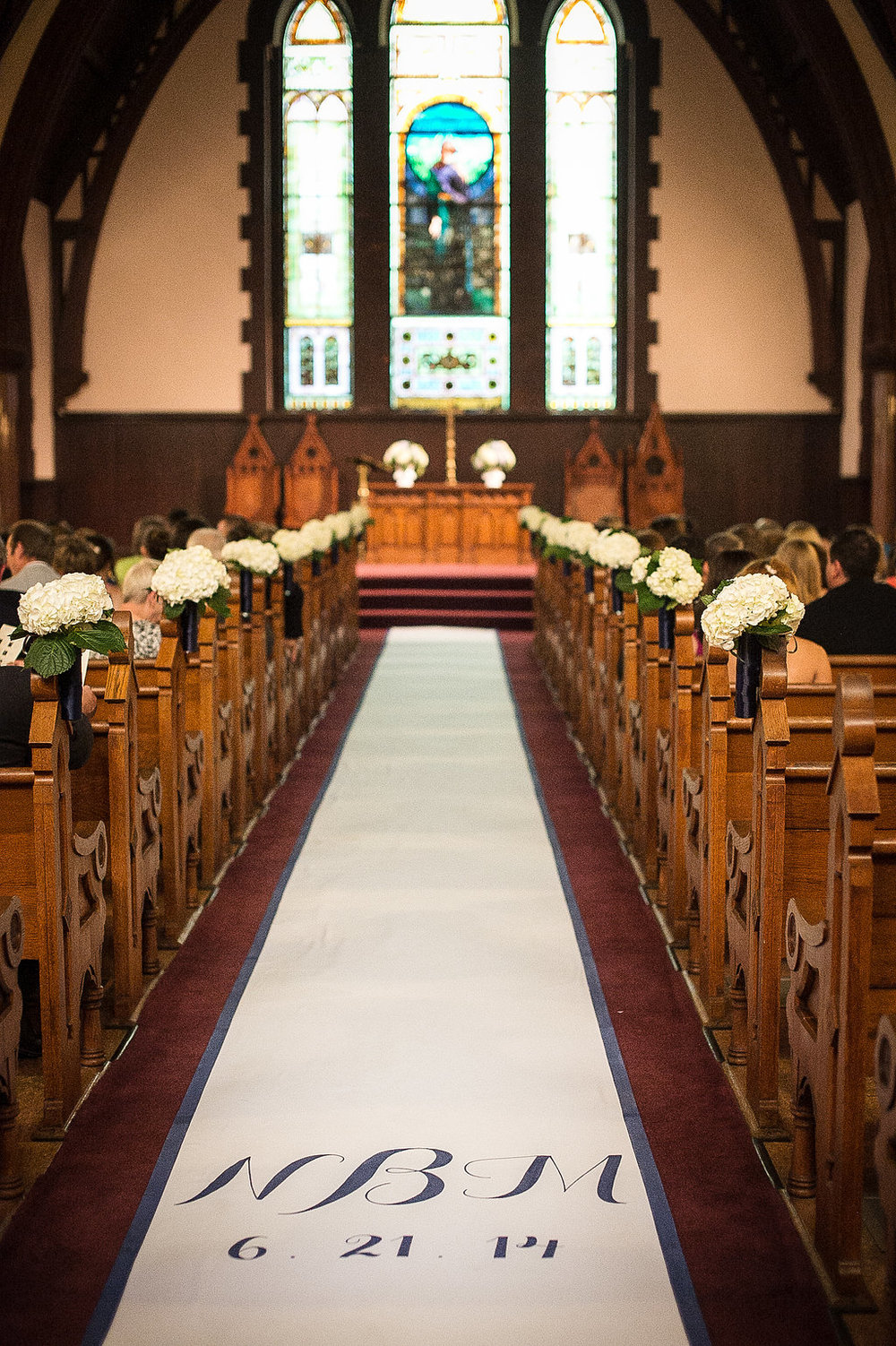 In the church we did a custom aisle runner in white with simple navy script of the couple's initials and the date, we did a navy stripe going down the sides of the aisle to keep with the theme, and mini bouquets of white hydrangeas lining the pews to create an elegant pathway for the bride.