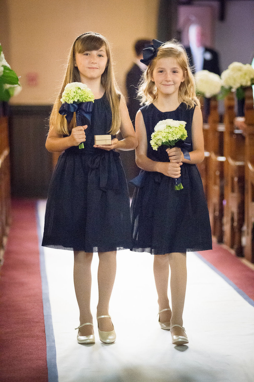 "Here are the ""ring bearer girls"" with small bouquets of white hydrangea and ranunculous tied with an exaggerated bow for a youthful look to the bouquets."