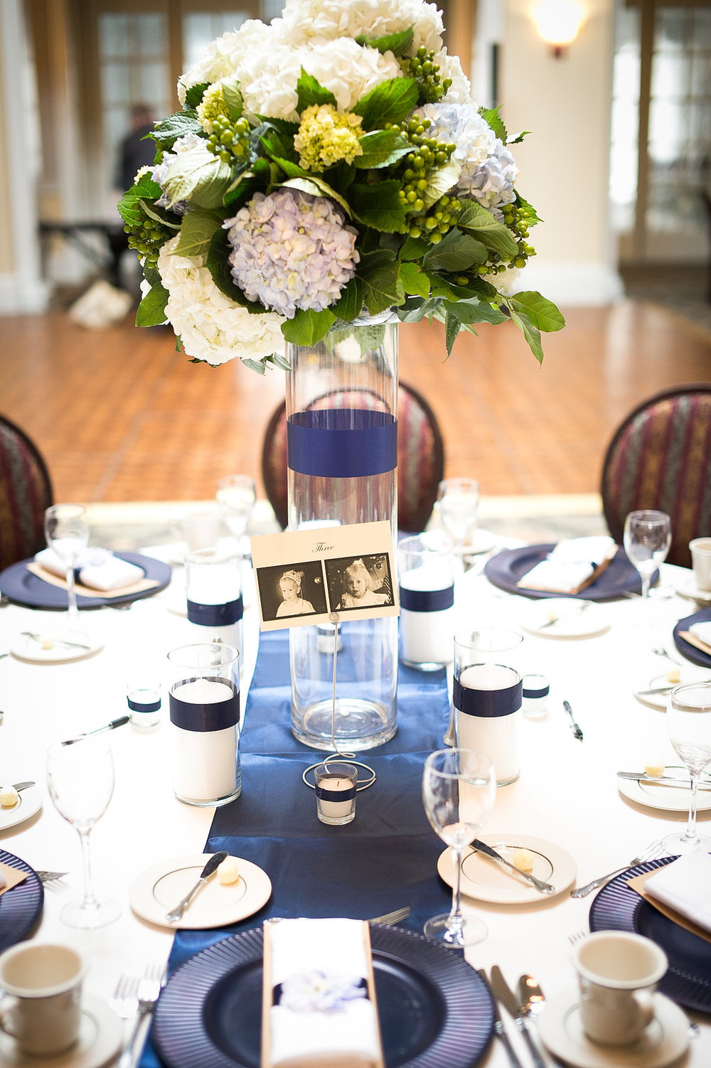 For the centerpieces we did a mix of white, blue and green hydrangeas with hypericum berries in a lush bouquet atop a cylinder vase with navy satin stripe over a mix of pillar and votive candles with matching navy satin stripe.