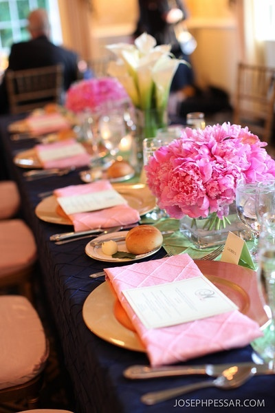 There was a modified head table for the bridal party, we did a collection of vases in round balls of peonies, orchids, and callas in varying square containers with votives scattered in between to create a beautiful lush table scape, which looked simpley gorgeous with the colorful pintuck linens and gold accented chargers and chivari chairs.