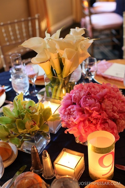Low monoflora bouquets of callas, peonies and cymbidiums with large square candles created a simple elegance to the table.