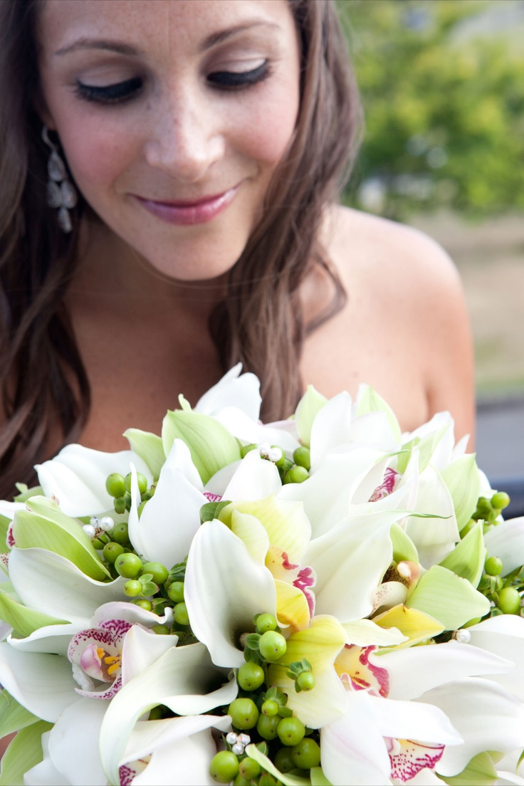 Bride's Bouquet a combo of green and white cymbidium orchids, a few white callas (also a very structured flower) highlighted by lime green hypericum, to create a simple and modern looking bouquet.