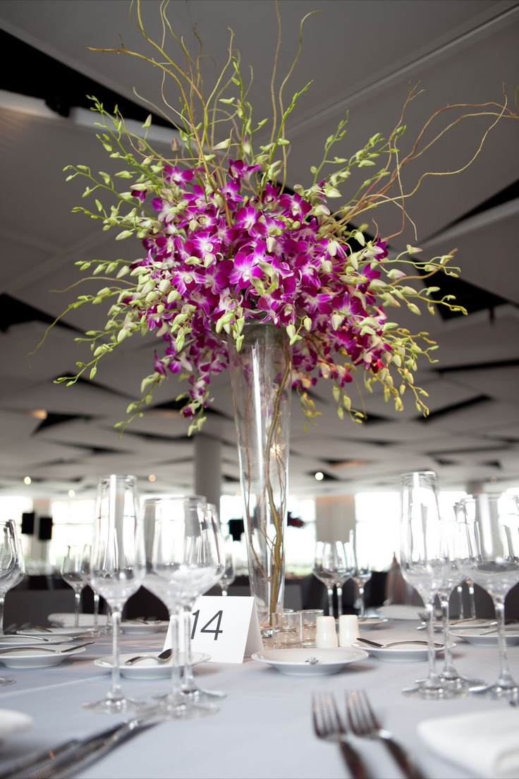 For the second style of centerpiece we did a simple spray of dendrobian orchids atop a fluted vase with striped curly willow branches woven in between the blossoms.
