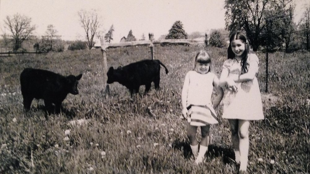 -          This is me on the left with my sister, hanging out with our Angus cows in Michigan.