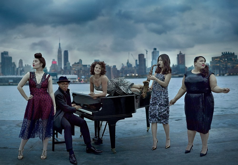 Some of the finest rising jazz vocalists, such as Tatiana Eva-Marie, 27 (far left), and Cyrille Aimée, 31 (reclining on piano), can trace their lineage to France, a jazz mecca. Here the two are joined on a barge on the Hudson River by pianist Aaron Diehl, 30, saxophonist Grace Kelly, 23, and singer Brianna Thomas, 32. Photograph by Mark Seliger. Source  Vanity Fair