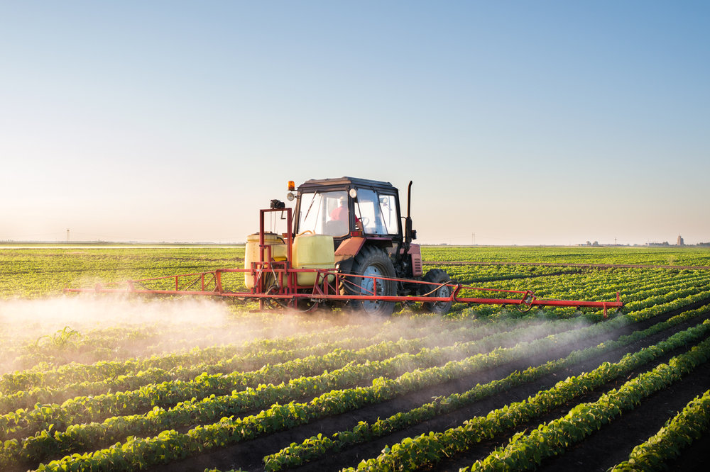 FARMER SPRAYS FERTILIZER ON HIS CROP