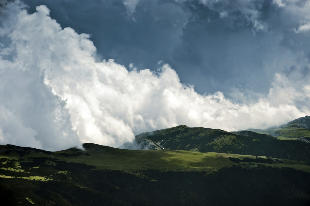 Clouds behind bright green alpine meadows by Horia Varlan