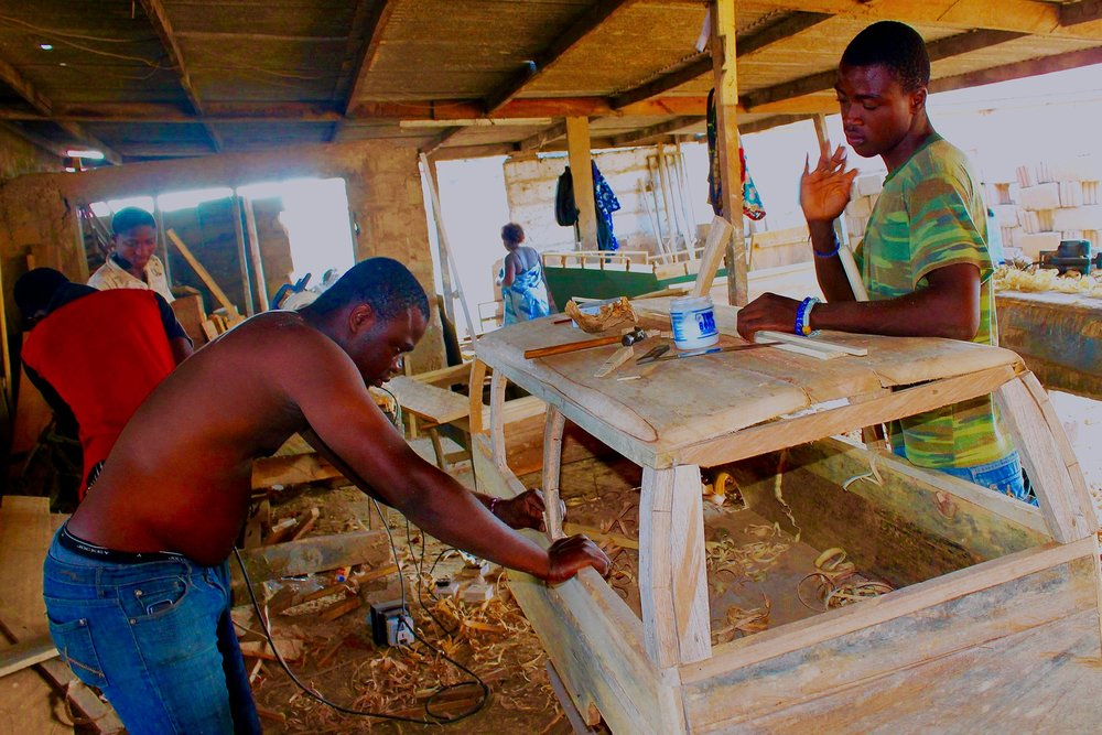Eric Anang (L) working with his crew at the Kane Kwei Carpentry Workshop in Accra, Ghana
