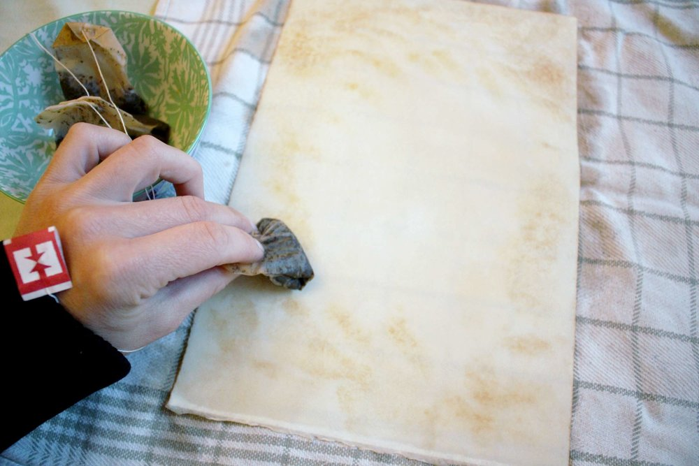 Using a teabag, sponge or paintbrush, add more tea to the paper to create a mottled effect.