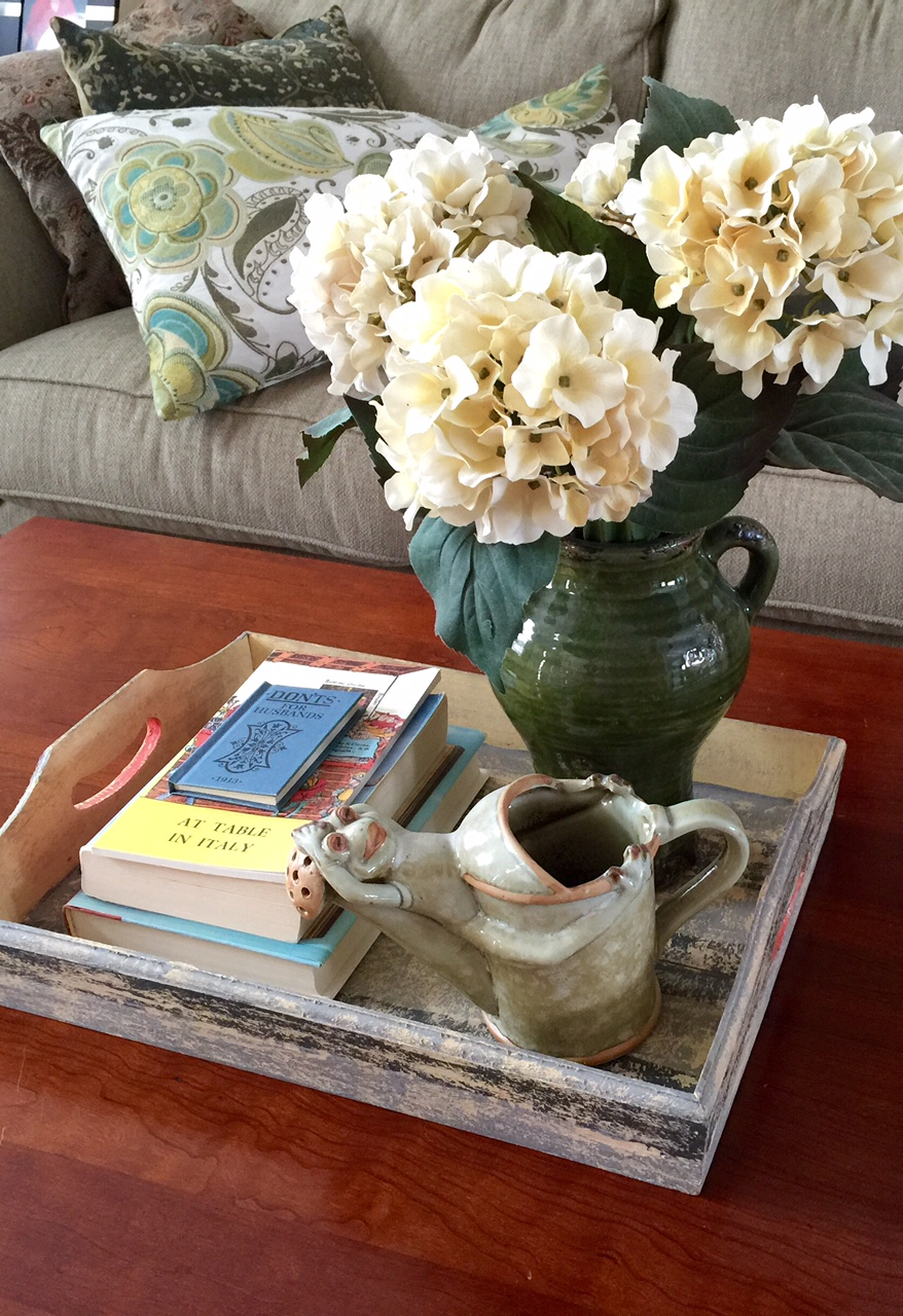 Use a coffee table tray to display your favorite books and add a floral sprig of spring to come.