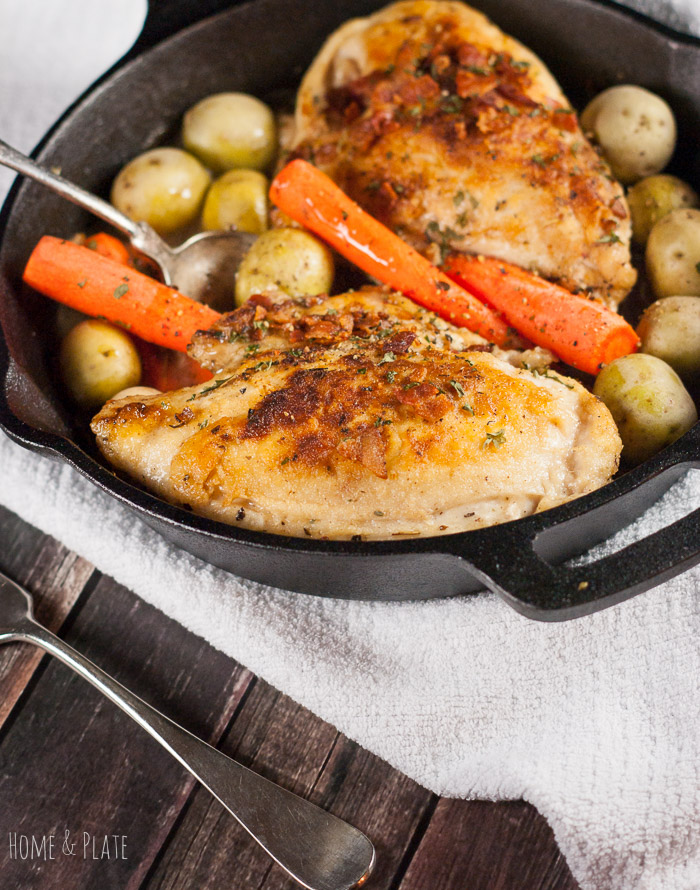 Cast Iron Skillet Roasted Chicken Breasts with Carrots & Potatoes | www.homeandplate.com | The chicken is nestled in a cast-iron skillet in a flavorful white wine sauce and paired with honey gold bite-size potatoes and tender carrots.