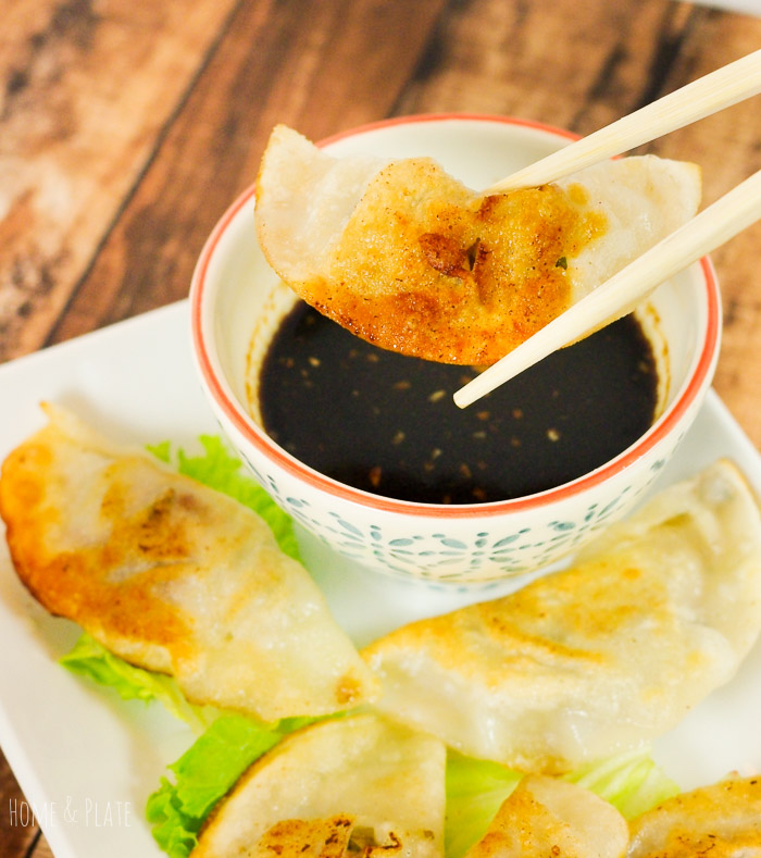 Homemade Chinese-Style Potstickers| www.homeandplate.com | Served with a splash of brown sugar and soy infused dipping sauce, these perfectly seasoned dumplings hide a juicy pork meatball inside.
