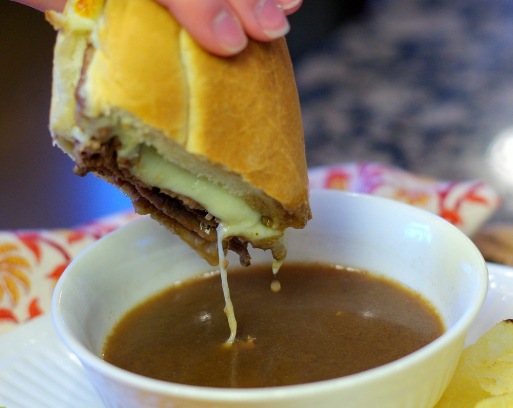 French Dip Sandwiches with Au Jus | www.homeandplate.com | Perfect for game day, this sandwich is sure to please the pickiest of palates. Slow simmer the French onion soup and serve alongside the sandwich in a ramekin or bowl.