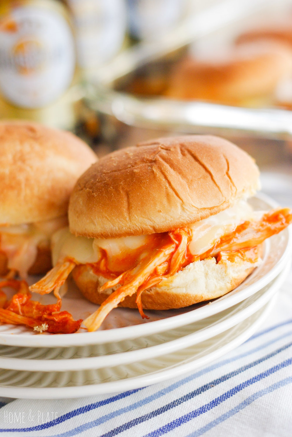 Msg 4 21+ | Buffalo Chicken Sliders| www.homeandplate.com | Plan a game day to remember by serving these spicy shredded buffalo chicken sliders oozing with melted cheese and pair of them with a cold premium pilsener. @krogerco @pepperidgefarm #ad #BeersAndBuns