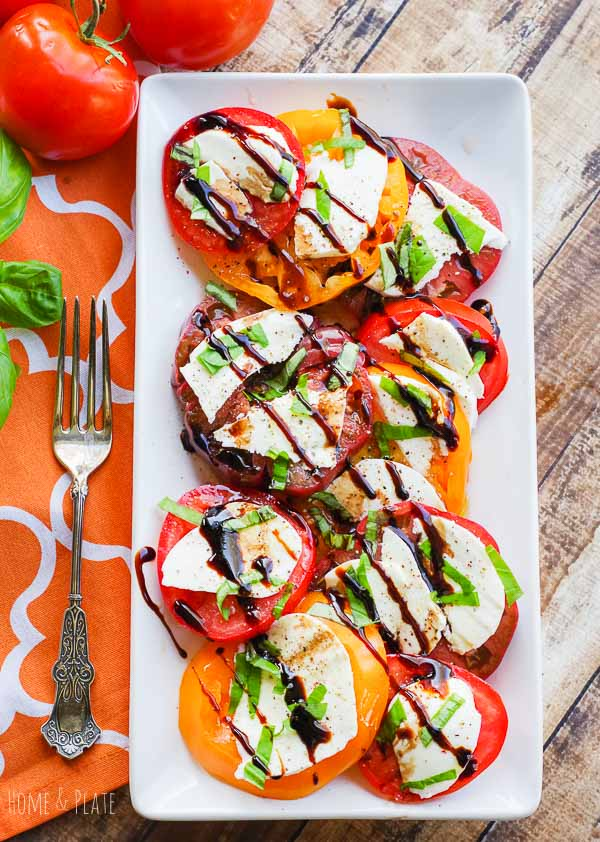 Tomato Caprese Salad | Home & Plate | www.homeandplate.com | A classic Italian salad of sweet tomatoes, creamy mozzarella and fresh picked basil is drizzled with olive oil and balsamic glaze for the ultimate summer side dish. #caprese #tomatoes