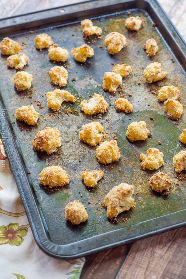 A baking tray with pieces of roasted cauliflower coated with Panko breadcrumbs and Parmesan cheese