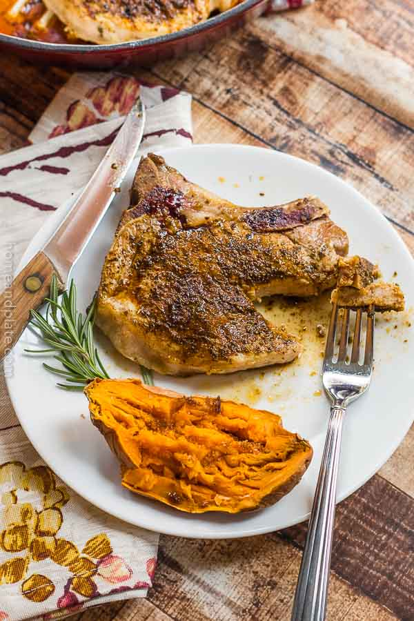 Ancho Chile Pork Chops   A juicy and tender pork loin chop rubbed in ancho chile powder on a plate with a baked sweet potato.