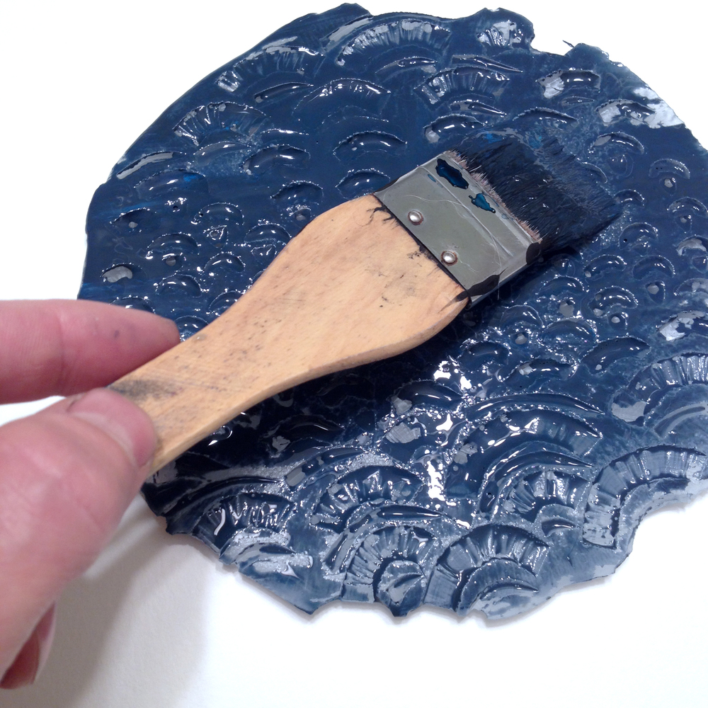 Apply a coat of paint or ink to the surface of the etching and cover with paper. Press with your fingers or wood.