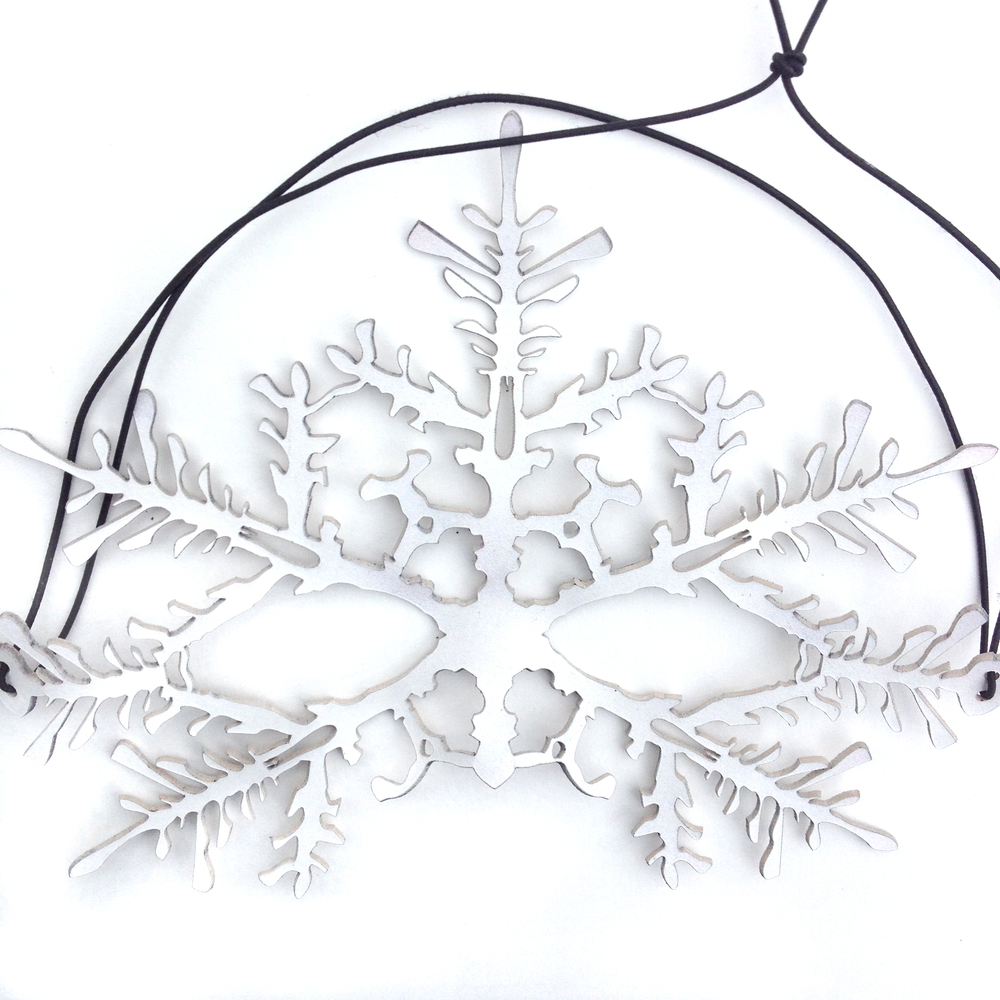 Bleached leather cut to resemble intricate snowflake branches and stems.