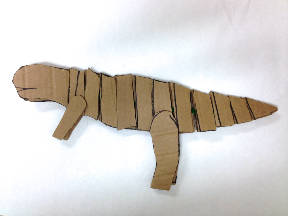 Bare, unpainted tyrannosaurs. A wire runs between both sides of the sideview silhouette. The segments allow for bend and movement.