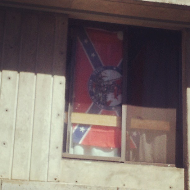 "Walking through the University of Southern Oregon and see this confederate flag in a dormitory window. Got a closer look and it has a seal in the middle that says ""shall rise again"". I'm assure this is not representative of everyone here. I think someone should address this…"