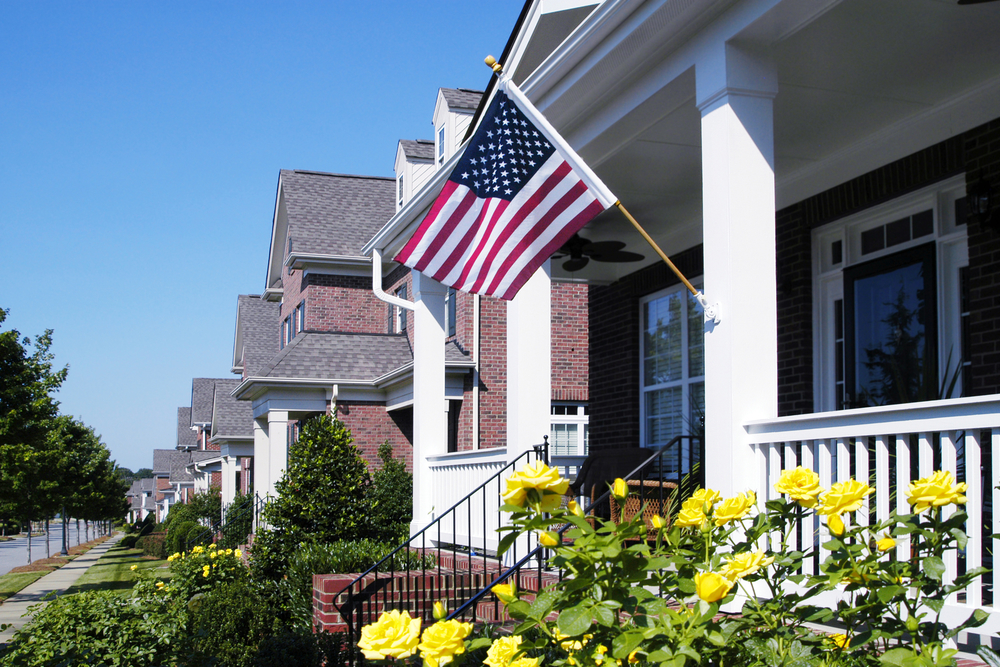 American-flag-on-the-front-porch-of-a-house-in-white.jpg