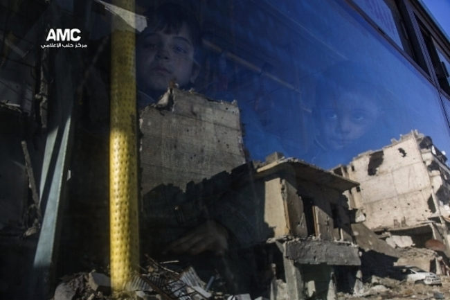 Child's reflection as buses leave Eastern Aleppo, Dec. 15, 2016