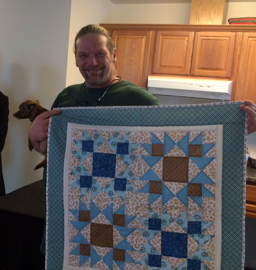 Shane in his new home with a housewarming quilt made by MDS women.