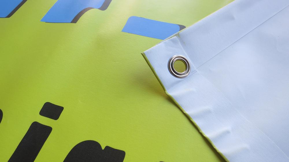 Konfektionierung - Die 4-farbig bedruckten Blachen werden Metallösen ausgerüstet und mit einem geschweissten Saum verstärkt.