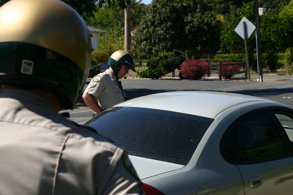 Motorcycle deputies communicate with a driver.