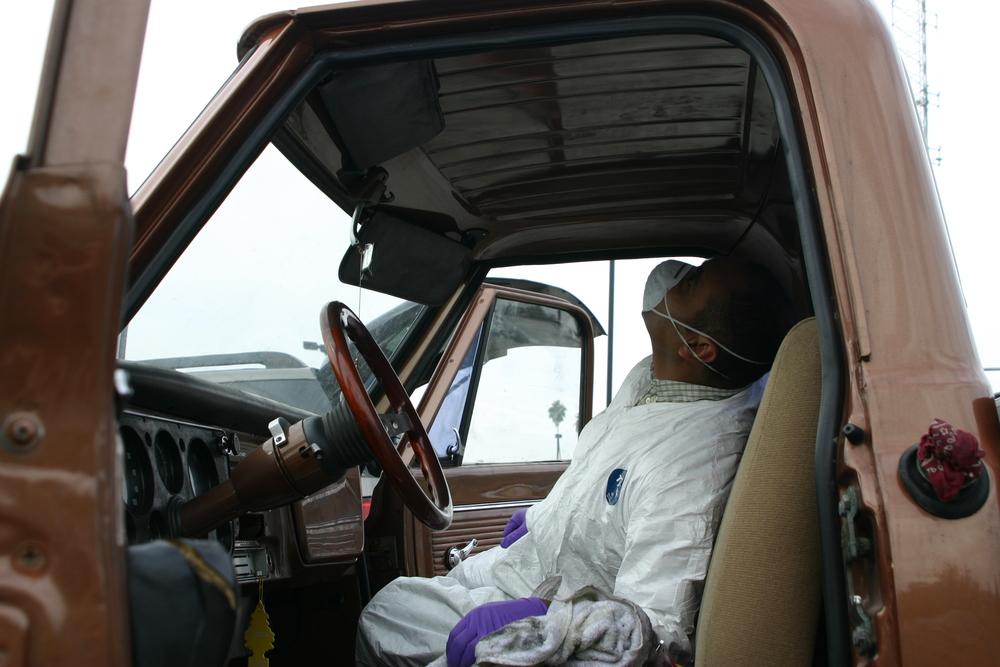 CSI detective examines vehicle for evidence.