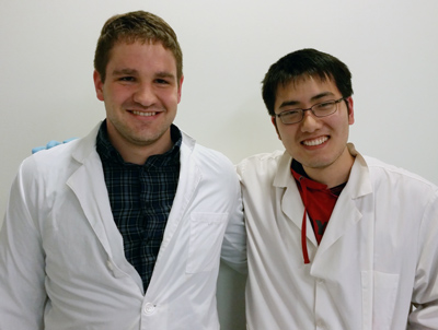 Picture of Shane Falcinelli and Iowis Zhu in lab coats.