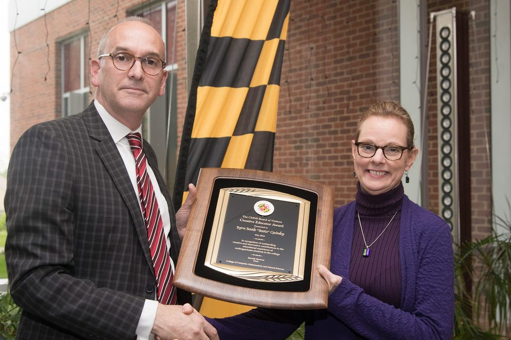 Dr. Boots Quimby accepting her Creative Educator Award from Associate Dean of Biology Dr. Bob Infantino.