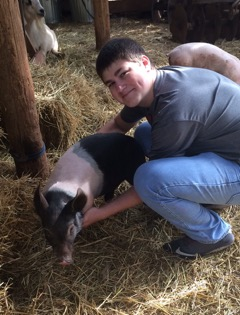 Jake Clements holding a pig in some hay.