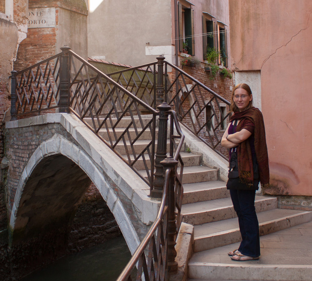 New Associate Direct, Dr. Sabrina Kramer standing next to a canal bridge in Venice, Italy.