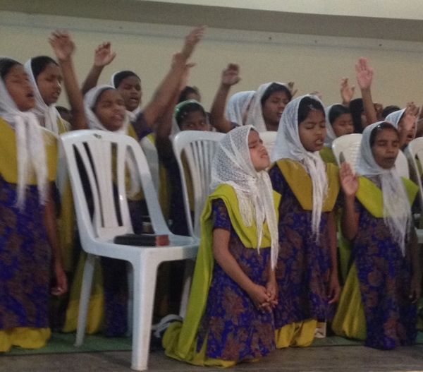 Students from the orphanage praying in worship