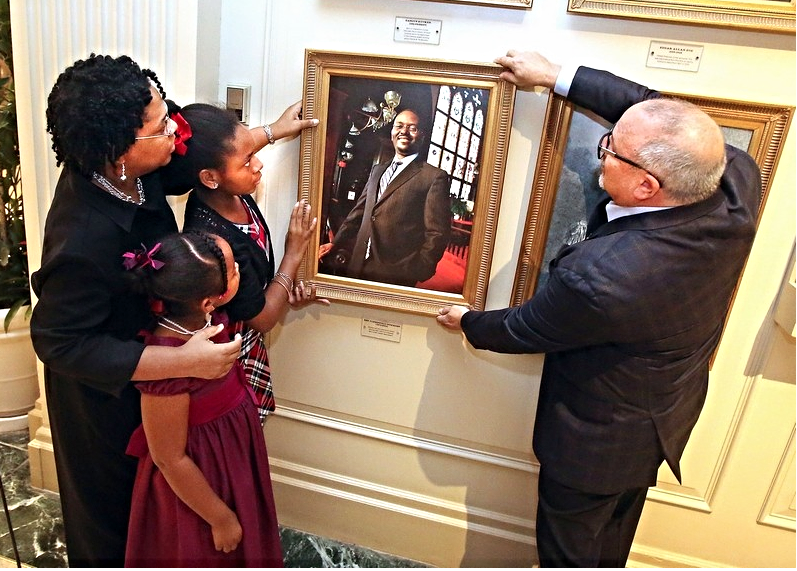 Mrs. Jennifer Pinckney, widow of Rev. Clementa Pinckney, and their daughters hang the portrait of their beloved husband and father at the Charleston Place Hotel    photo credit: Brad Nettles/PostandCourier