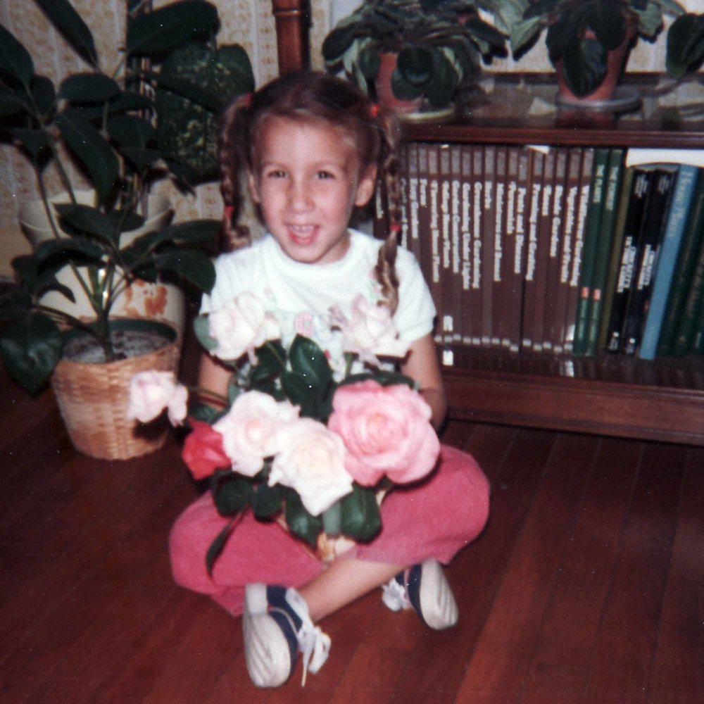 Anne as a child with an armful of roses