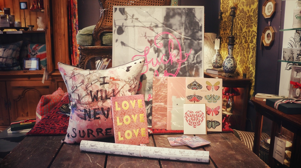 """Fuck It"" pink print $120, ""Love, Love, Love"" notebook $15, Pug gift wrap $3, ""I Will Never Surrender"" hand printed silk pillow $125, Moth, Cat & pink notebooks $9.95 ea., ""I Feel Pretty"" coaster $6.50 ea."