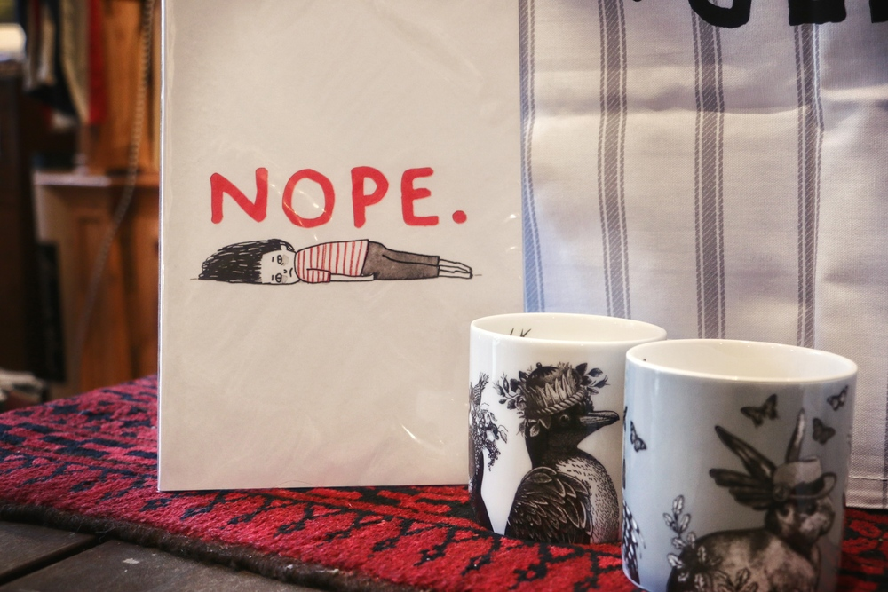"Bone China mugs $28, ""Nope"" notebook $9.95."