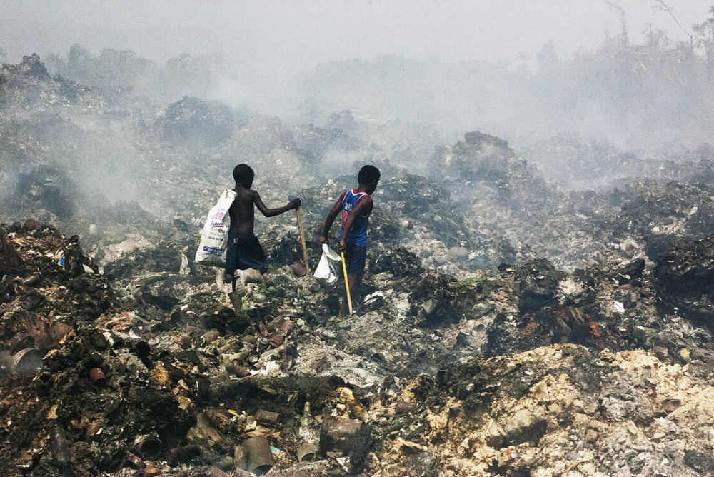 """""""Everyday Life""""  Two Haitian kids trek through the garbage and smoke looking for food or items they can use.The smoke is caused by fires started when the sun heats up and ignites compacted garbage over. Many make shift shelters were burned up in the fire. The only benefit is that the smoke caused by the fire helps drive away the abundance of flies that share the food and waste dumped there."""