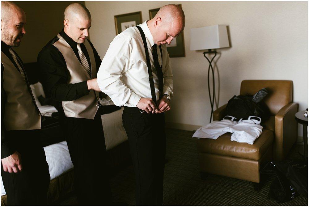 groom-putting-on-suspenders-embassy-theatre-weddingfort-wayne-indiana-photographer