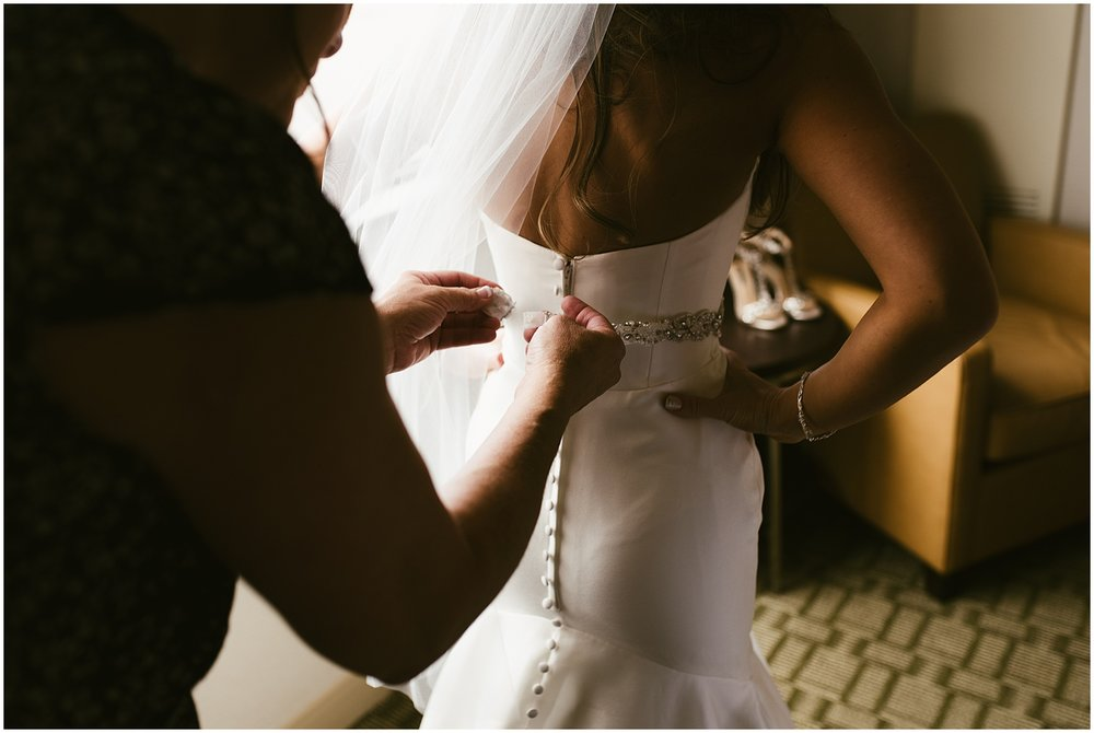 stella-york-gown-bride-attaching-belt-hilton-hotel-fort-wayne-indiana