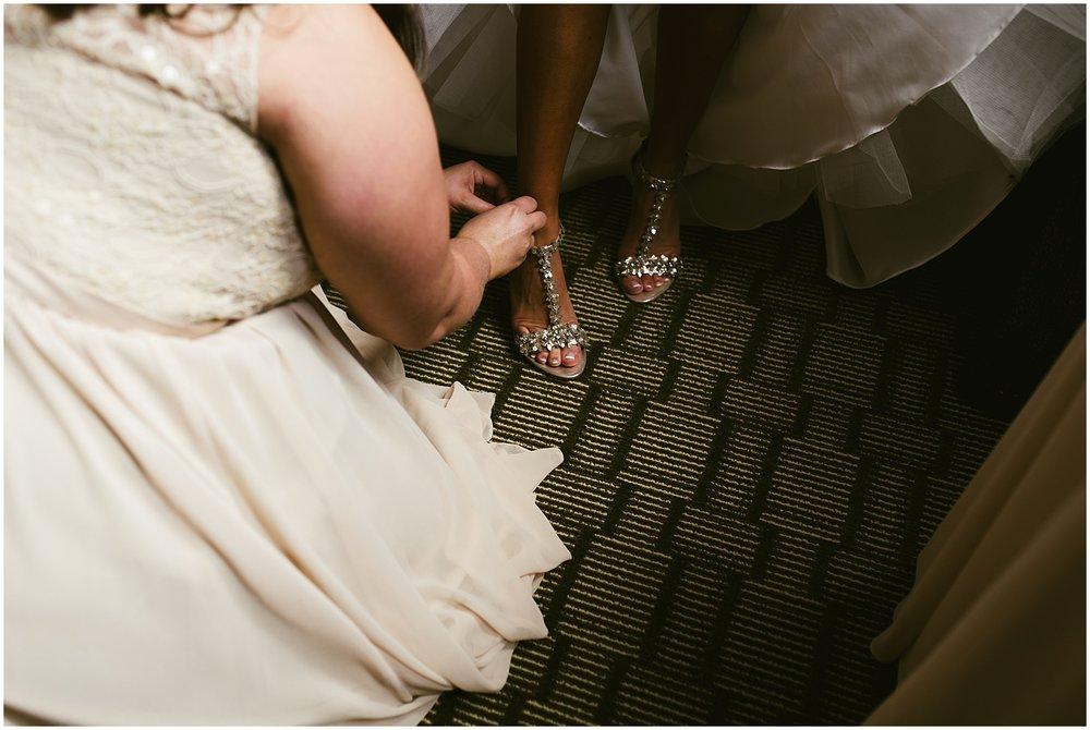 bride-putting-on-shoes-hilton-hotel-fort-wayne-indiana-wedding-photographer