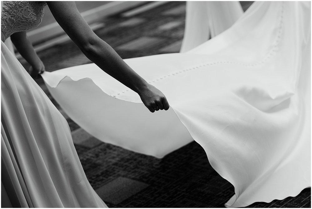 bridesmaid-fixing-dress-bride-father-embracing-aisle-center-wedding-fort-wayne-indiana