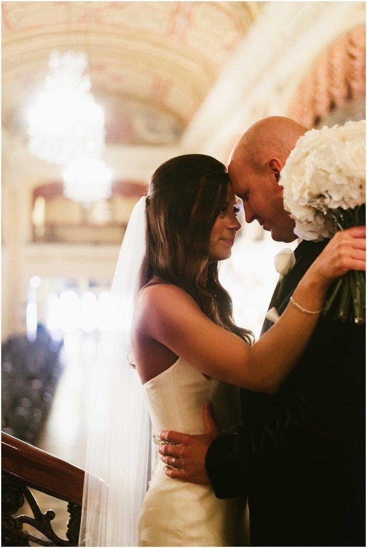bride-groom-bouquet-touching-forehead-embassy-theatre-lobby-romantic-wedding